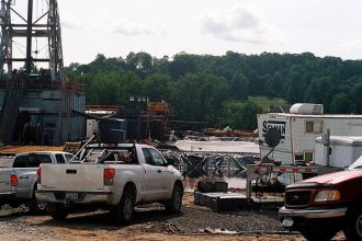 a natural gas drilling rig surrounded by trucks