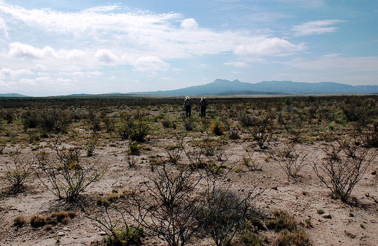 Two ranchers walk across parched dried soil in Culberson County, Texas.