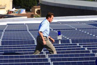 Former California Gov. Arnold Schwarzenegger walks between solar panels after at