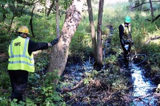 Cleanup experts work to remove oil near the Kalamazoor River spill site,