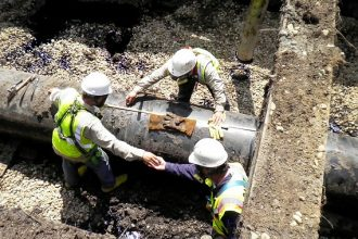 Technicians prepare pipe before cutting and removing the section from the Enbrid