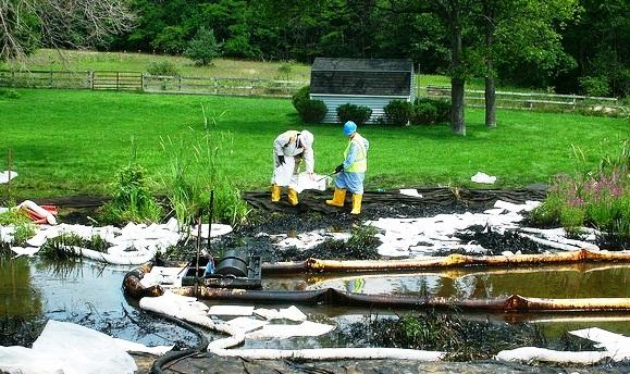 Crew clad picks up contaminated soil along the banks of the Kalamazoo River.
