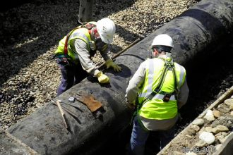 Technicians prepare the pipe before removing the ruptured section of 6B.
