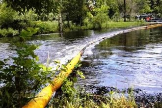 Yellow containment boom stretched across the Kalamazoo River following the Enbri