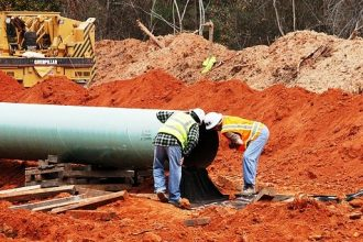 Workers examine pipe being used for the southern leg of the Keystone XL pipeline