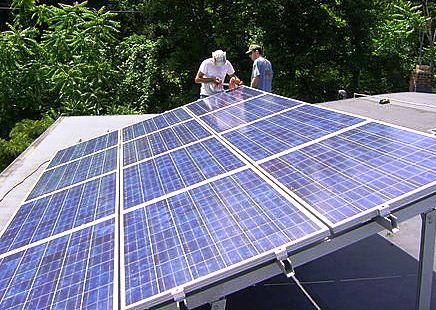 Workers installing solar panels on a roof near Poughkeepsie, N.Y.