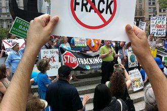 Protester holds a sign at an anti-fracking rally.