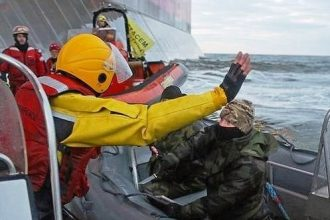 A Russian Coast guard officer points a knife at a Greenpeace activist.