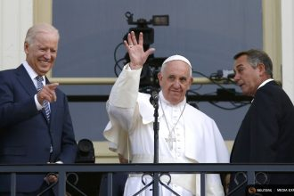 Pope Francis, flanked by Vice President Joe Biden and House Speaker John Boehner, waves to the crowd at the Capitol.