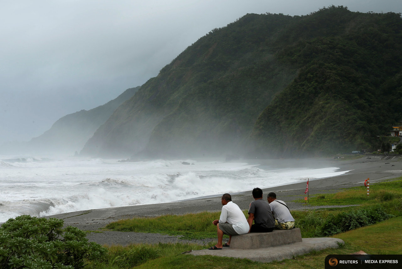 Men watch the ocean as super typhoon Nepartak nears the coast of Taiwan