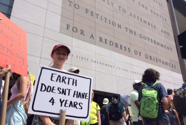 Climate marchers in front of a wall engraved with the First Amendment
