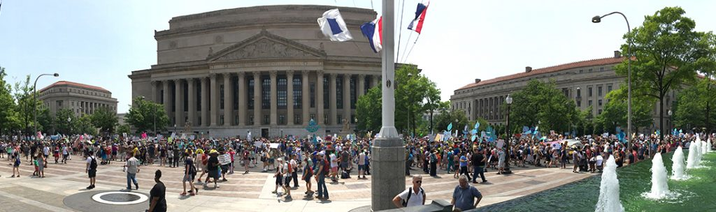 Climate marchers pass the National Archives