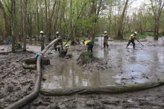 Workers begin the long process of cleaning mud from a pipeline construction spill out of wetlands.