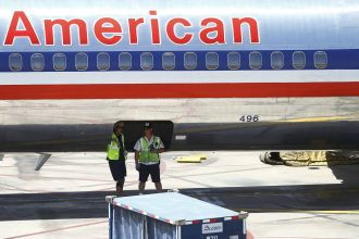 Airport ground crews wait in the shade of an airplane grounded by excessive heat in Phoenix. Credit: Josh Lott/Getty Images