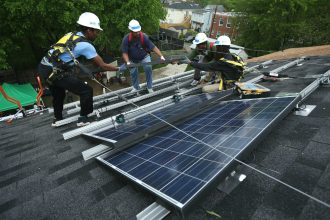 Solar panel installers at work in Washington, D.C. Credit: Alex Wong/Getty Images