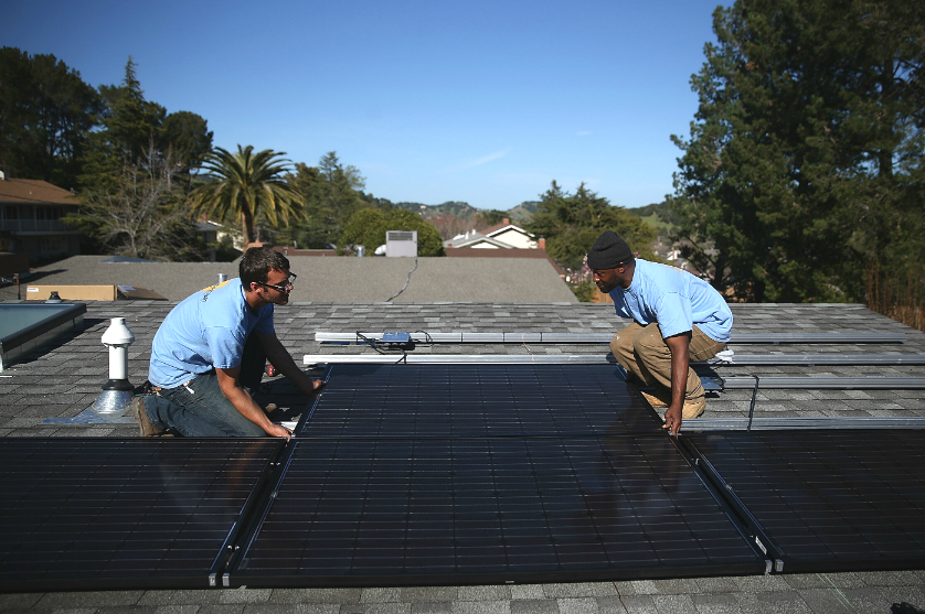 Solar panel installers work on a rooftop in California. Credit: Justin Sullivan/Getty Images