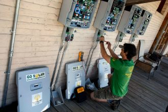 A solar company wires control boxes for solar panels and building's roof in Gainesville, Florida. Credit: Joe Raedle/Getty Images