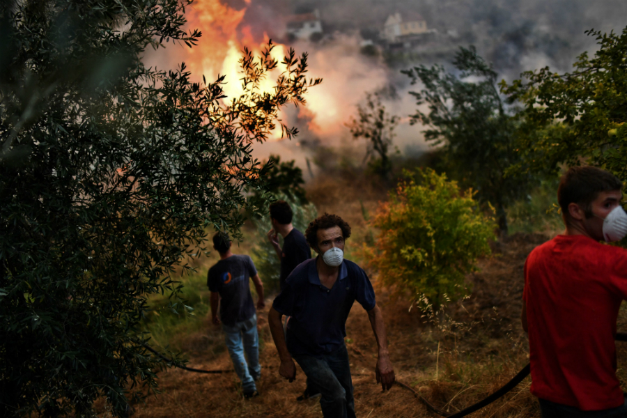 Residents fight one of several wildfires burning in Portugal in the summer of 2017. Credit: Patricia de Melo Moreira/AFP/Getty Images
