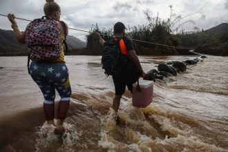 People use a rope line to cross the San Lorenzo de Morovis river to deliver food and supplies to relatives. Flooding from Hurricane Maria destroyed the bridge. Credit: Mario Tama/Getty Images