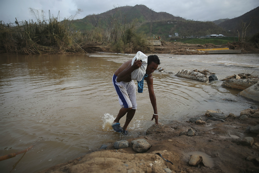 Jose Acevedo crosses a river on foot after the bridge near Morovis, Puerto Rico, was washed away Hurricane Maria on September 27. Credit: Joe Raedle/Getty Images