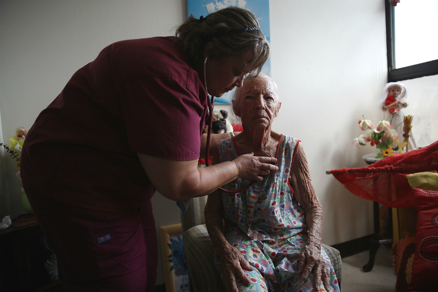 A doctor from a First Medical Relief team conducts health check-ups in an assisted-living center.  Credit: Joe Raedle/Getty Images