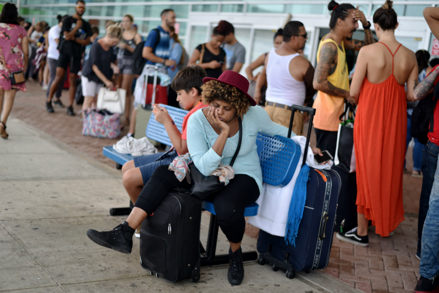People waited in long lines at San Juan's main airport for seats aboard the limited number of flights off the island. Credit: Hector Retamal/AFP/Getty Images