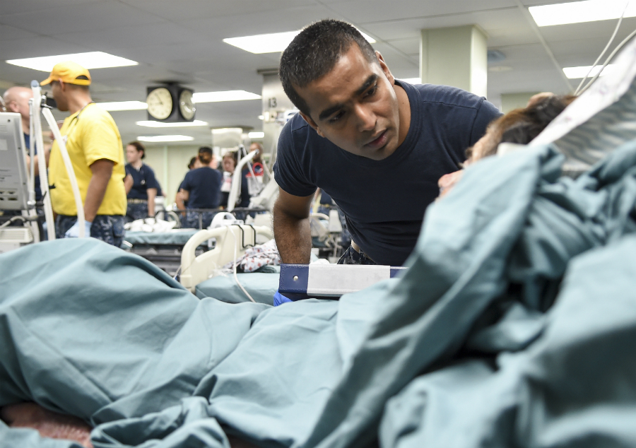 Lt. j.g. Shiju SantaNivas, an intensive care nurse from Walter Reed National Military Medical Center, treats a patient aboard the USNS Comfort in Puerto Rico after Hurricane Maria. Credit: Specialist 2nd Class Stephane Belcher/U.S. Navy