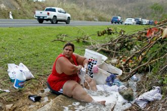 With no running water, Puerto Rico residents in some areas resorted to washing clothes in creeks and drainage ditches. Credit: Ricardo Arduengo/AFP/Getty Images