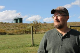 Brian Latkanich stands in his yard with the fracking well behind him. Credit: Anna Belle Peevey