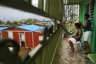 Mirian Medina does her granddaughter's hair on her front porch. Blue tarps cover damaged roofs on many of the homes in her San Isidro neighborhood, which remained with out power weeks after the storm. Credit: Mario Tama/Getty Images