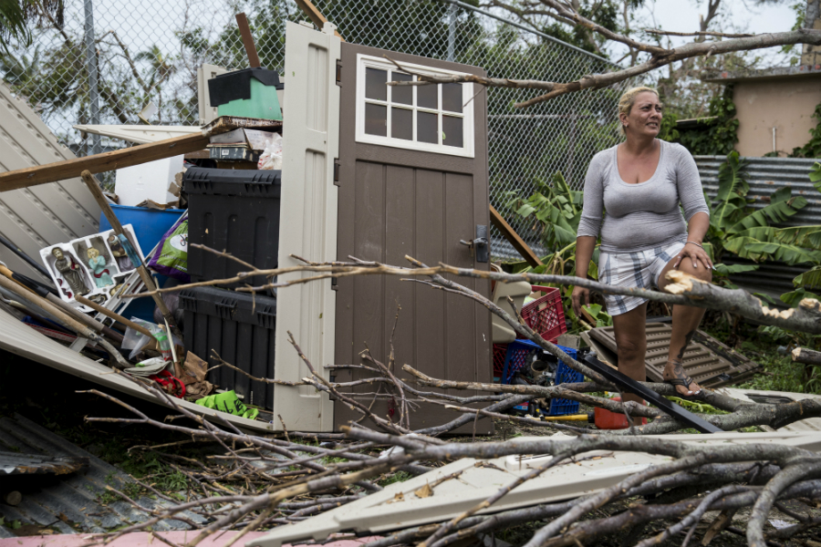 Hours after Hurricane Maria left Puerto Rico, a resident of San Juan looked over what remained of her property. Homes were stripped of their roofs and walls across the island. Credit: Alex Wroblewski/Getty Images