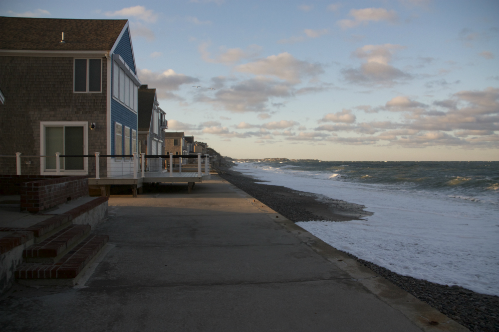 There's little beach left at high tide by Don Hourihan's house in Humarock, where waves washed up to a concrete seawall he built with his neighbors in the 1970s. Credit: Nicholas Kusnetz/InsideClimate News