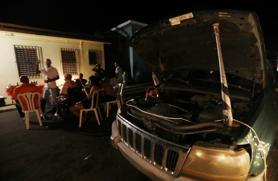 A car battery provides power for a Christmas Eve gathering in Puerto Rico. Credit: Mario Tama/Getty Images