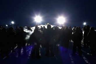 People protesting the Dakota Access Pipeline path under the Standing Rock tribe's water supply approach a police barricade. Credit: Scott Olson/Getty Images