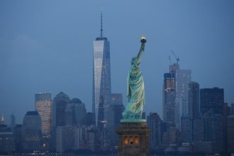New York City skyline at dusk with the Statue of Liberty. Credit: Drew Angerer/Getty Images