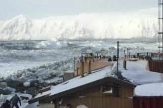 Waves batter Little Diomede Island, where coastal communities are normally protected by ice through the winter. This year, the ice buffer melted early. Credit: Frances OzennaWaves batter Little Diomede Island, where the coastal community is normally prote