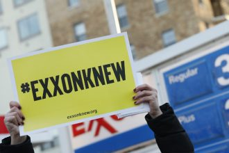 """Protesters hold """"Exxon Knew"""" signs in Washington, D.C. Credit: Aaron P. Bernstein/Getty Images"""