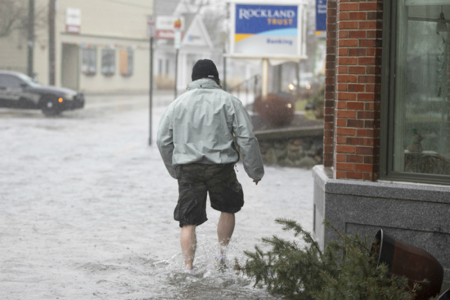 A man walked along Scituate's flooded Front Street as a nor'easter slammed the New England and Mid-Atlantic coast with heavy snow, rain, strong winds and coastal flooding. Credit: Scott Eisen/Getty Images