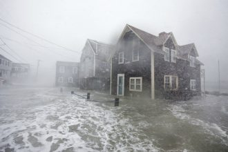 Powerful waves washed over the tops of houses in Scituate, Massachusetts, and flooded the streets. Credit: Scott Eisen/Getty Images