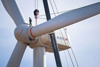 A crane lifts blades to be added to a wind turbine. Credit: Dennis Schroeder/NRELA crane lifts a blade being attached to a wind turbine. Credit: Dennis Schroeder/NREL