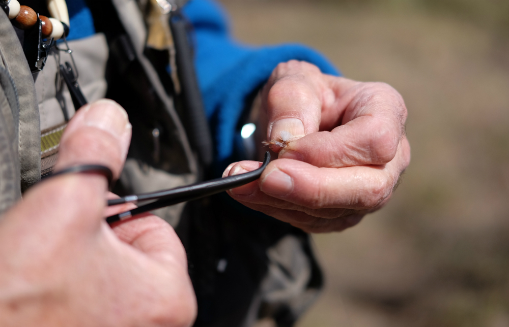 Craig Fellin prepares a fly for casting into the Big Hole River. The trout are more likely to bite when the water temperature is between 45 and 65 degrees Fahrenheit, he says. Credit: Meera Subramanian