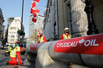 Demonstrators criticize Canadian Prime Minister Justin Trudeau over his support from the oil industry using signs that read Crudeau Oil on a fake pipeline. Credit: Tolga Akmen/AFP/Getty Images