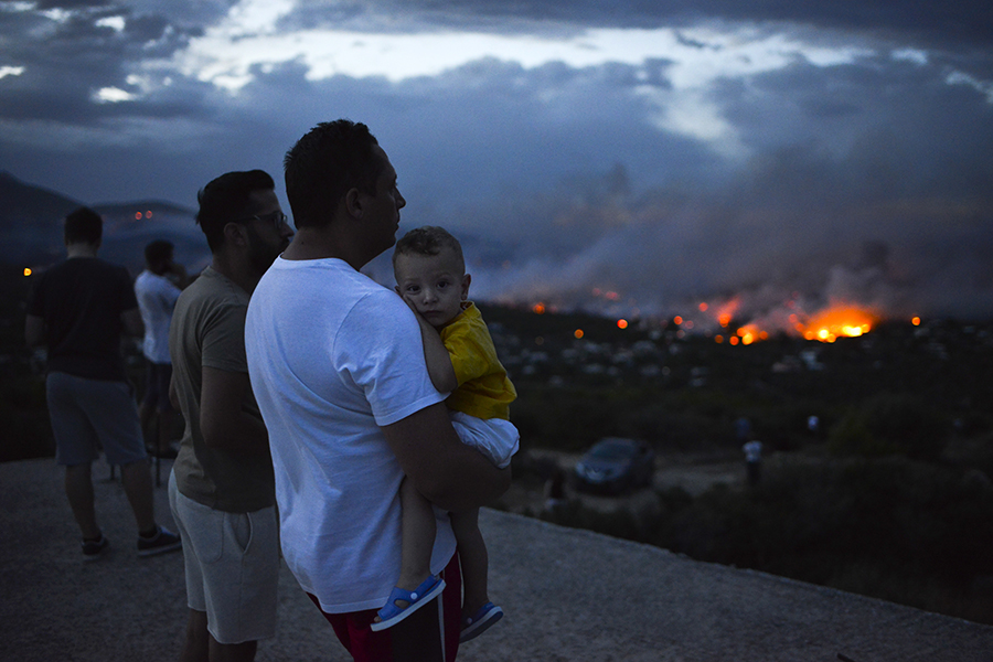 Residents watch as fires burn into the city of Rafina, near Athens, on July 23. Credit: Angelos Tzortzinis/AFP/Getty Images