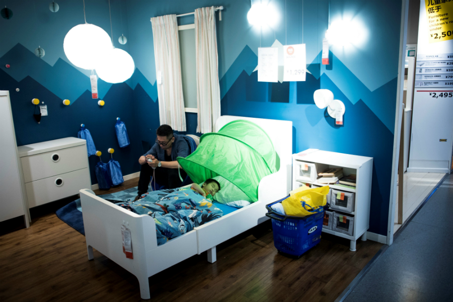 A father escapes the heat in Shanghai by letting his son sleep in an air-conditioned Ikea store. Credit: Johannes Eisele/AFP-Getty Images
