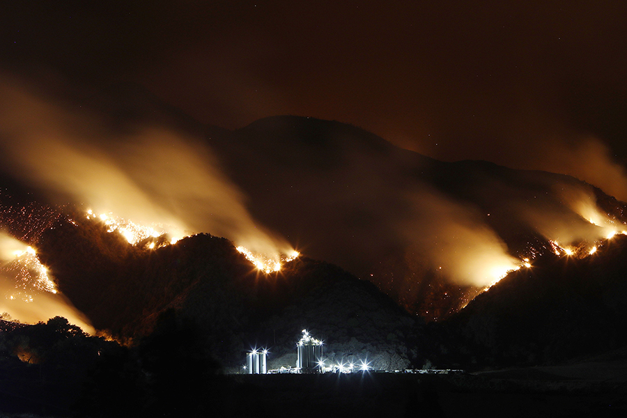 A wildfire burns in the hills near an industrial facility outside Corona, California, in August 2018. Credit: Mario Tama/Getty Images