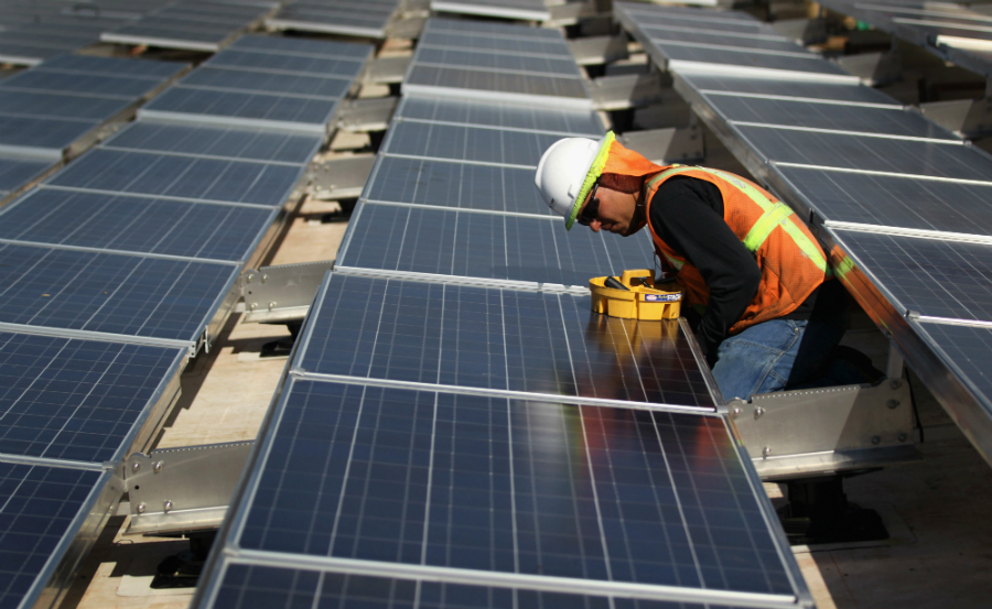 Workmen installs solar panels in Colorado. Credit: John Moore/Getty Images
