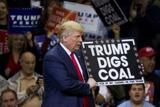 """Donald Trump holds a """"Trump Digs Coal"""" sign at a rally. Credit: Dominick Reuter/AFP/Getty Images"""