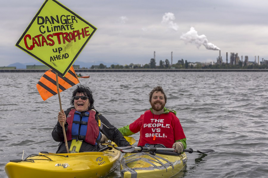 Kayakers, part of a flotilla calling for pro-climate policies in Washington state, protest outside a refinery near Anacortes. Credit: John Duffy/CC-BY-2.0