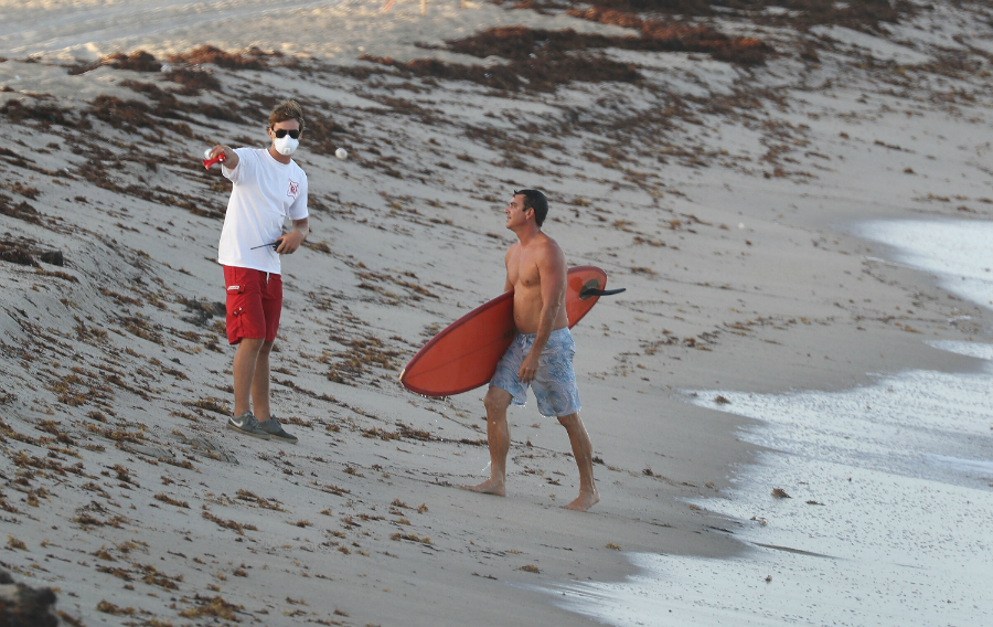 A lifeguard wearing a protective mask asks a surfer to leave the ocean after Palm Beach County officials closed all area beaches due to red tide earlier this month. Credit: Joe Raedle/Getty Images