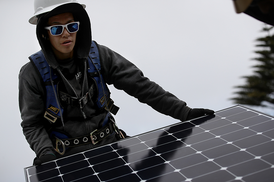 A solar installer on a rooftop. Credit: Justin Sullivan/Getty Images